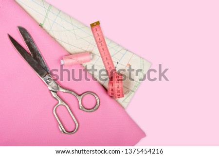 Tailoring. Sewing accessories and accessories for sewing and needlework. Scissors, centimeter, pattern, spool of thread and fabric of pink color on a pink background. Isolate, Flat Lay, Copy Space