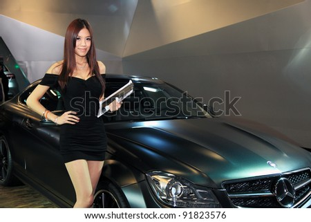 TAIPEI - JAN 1:  Female presenter model with Mercedes-Benz C 63 AMG Coupe' Performance Studio car on display at the 19th TAIPEI INT'L AUTO SHOW on January 1, 2012 in Taipei Taiwan