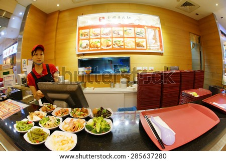 TAIPEI, TAIWAN - June 8: a girl serving at Beef Noodle in a Food court at a shopping mall on June 8, 2015, Taipei, Taiwan.  Beef Noodles is one of the many popular meal in Taiwan