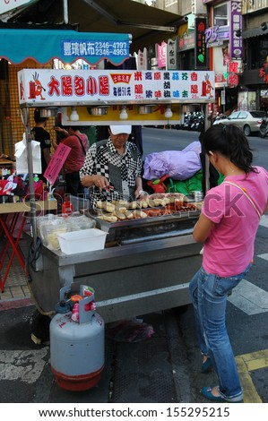 TAIPEI, TAIWAN-JUNE 14: Customer buys street food from street vendor on June 14, 2013 in Taipei, Taiwan. There are over 100 night markets scattered throughout the city.