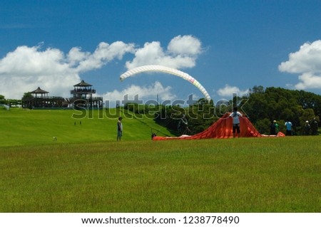 Taitung City, Taiwan - July 20, 2008: Blue sky and white clouds and green hills, gliding wings in a curved arc-shaped path through the upward grassland, a happy journey. #1238778490