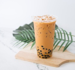 Taiwan milk tea with bubble plastic glass on wood background