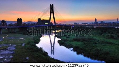 Taiwan, New Taipei City, the beautiful twists and turns of the river, reflecting the sky, bridges, sunrise and sunset city beautiful scenery. #1123952945
