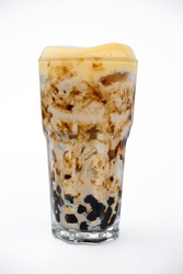 Taiwan tea with milk and pudding and black boba  in a transparent glass isolated on white