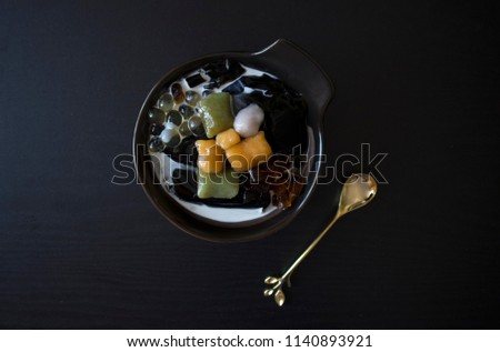 Taiwanese Dessert with Gold Spoon, Singapore dessert, Asian dessert on Black Table with Copy Space. Taiwanese Dessert with Grass Jelly, Taro Balls, Sweet Potato Balls, Fresh Milk, Boba on Wooden Table