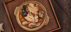 Taiwanese food - Homemade delicious sesame oil chicken soup in a bowl on dark wooden table background.