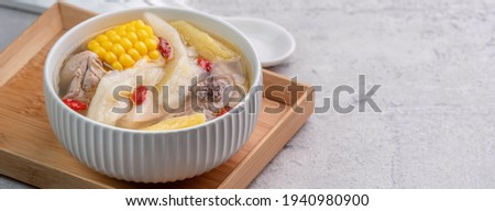 Taiwanese homemade delicious chicken soup food in a bowl with pineapple, bitter gourd and sweet corn on cement gray table background. Stock photo ©