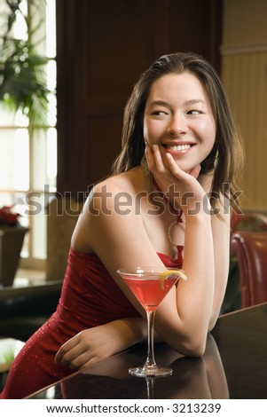 Taiwanese mid adult woman in red dress smiling and standing at bar with drink.