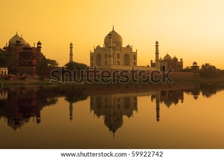 Taj Mahal at sunset reflected in the calm yamuna river.