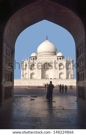 Taj Mahal mausoleum seen from inside mosque at India's Agra. Dark arch with huge doors frames white marble monument against blue skies