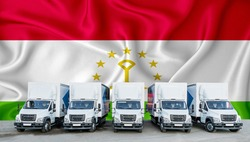 Tajikistan flag in the background. Five new white trucks are parked in the parking lot. Truck, transport, freight transport. Freight and logistics concept