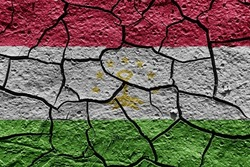 Tajikistan flag on a mud texture of dry crack on the ground