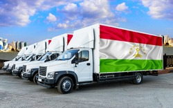 Tajikistan flag on the back of Five new white trucks against the backdrop of the river and the city. Truck, transport, freight transport. Freight and Logistics Concept