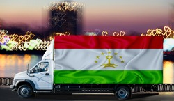 Tajikistan flag on the side of a white van against the backdrop of a blurred city and river. Logistics concept