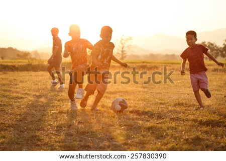 TAK, THAILAND - MARCH 4, 2015:Rural children are playing football in the sunshine day in a village in Tak, Thailand - Shutterstock ID 257830390