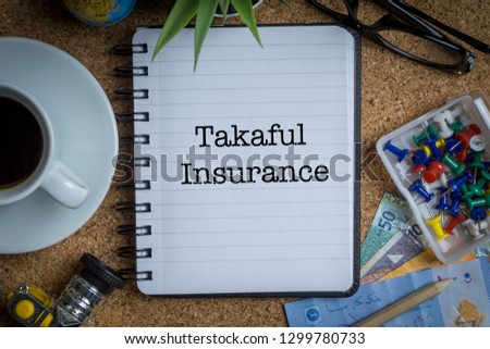 TAKAFUL INSURANCE ( or ISLAMIC INSURANCE) inscription written on book with globe,eyeglasses, calculator, camera, pencil and vase on wooden. Business concept Stock fotó ©