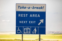 take a break, Rest area in the next exit, Tidy man, toilets, Special needs symbols., Information Road blue Sign against yellow prairies and plains