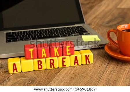 Take a Break written on a wooden cube in a office desk