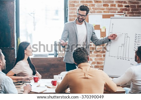 Take a look at our results! Handsome young man in glasses standing near whiteboard and pointing on the chart while his coworkers listening and sitting at the table  #370390049
