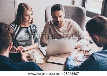 Take a look at this chart! Young handsome man using laptop while sitting at the office table on business meeting with his coworkers