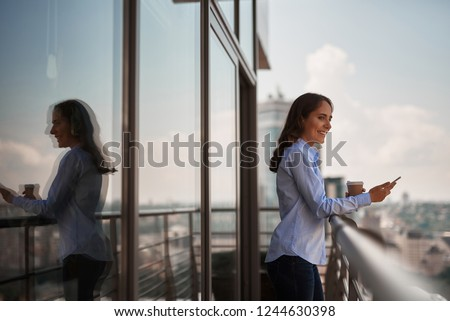 Take a pause. Portrait of smiling businesswoman enjoying city view with smartphone in hand while having coffee break on office balcony. Copy space on left #1244630398