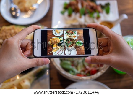 Take a photo of a smartphone for lunch or dinner. Woman taking picture with phone. Posting or sharing popular food for social media. Photo stock ©
