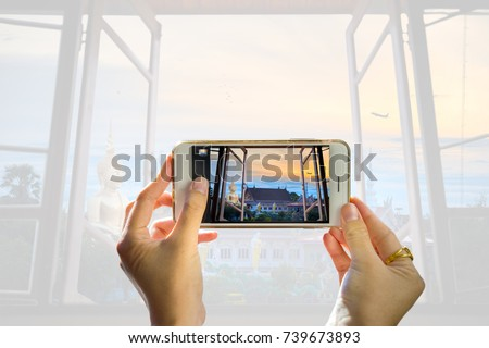 Take a picture of someone taking a cellphone through a window of your home. While photographing a temple with a large Buddha image telephone towers and Solar Cell,And the background blurred.