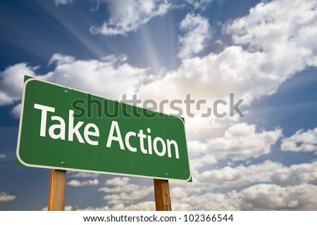 Take Action Green Road Sign with Dramatic Clouds, Sun Rays and Sky.