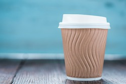 Take away coffee plastic cup on wooden background with space for text or advert