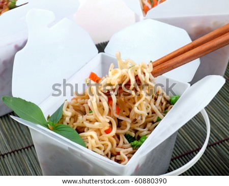 Take away egg noodles on chopsticks in a take away container.