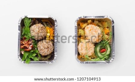 Take away lunch. Two portions of meatballs with vegetables in foil containers, isolated on white background, top view