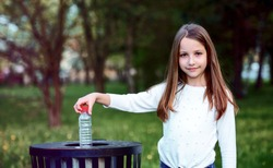 Take care about your environment. Little girl throwing bottle into the trash. Ecology concept
