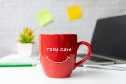 Take Care for healthy life office.  Close Coffee red cup for relax and take a break supplies and laptop background.  Lifestyle Health Concept