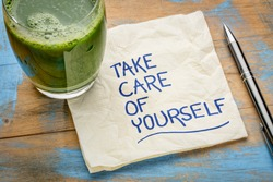 take care of yourself - inspirational handwriting on a napkin with a glass of green juice