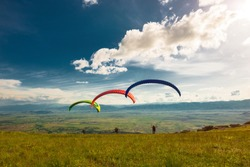 take-off of three paragliders
