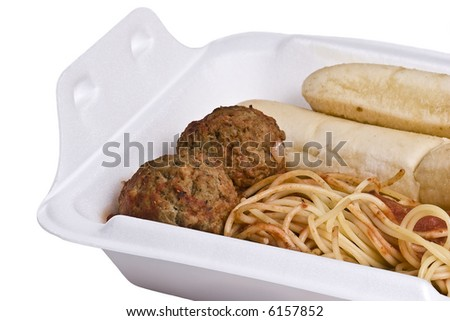 Take out container filled with left over spaghetti and meatballs with seasoned breadsticks.  Isolated on white.