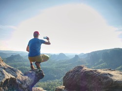 Take phone photo. Hiker sit at edge for taking selfie picture. Share picture.
