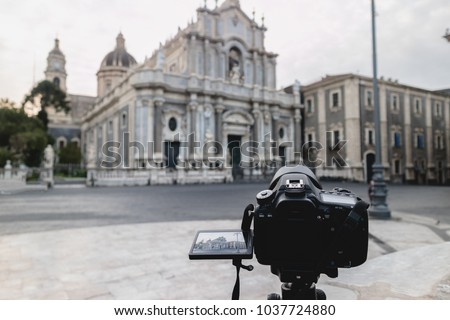 Take photos or shoot video with a reflex camera on an easel in the Piazza Duomo in Catania, near the elephant fountain, symbol of Catania #1037724880