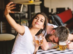 Take selfie to remember great event. He appears too weak for her. Woman making fun of drunk friend. Man drunk fall asleep table and girl with full beer glass. Girl taking selfie photo drunk boyfriend.