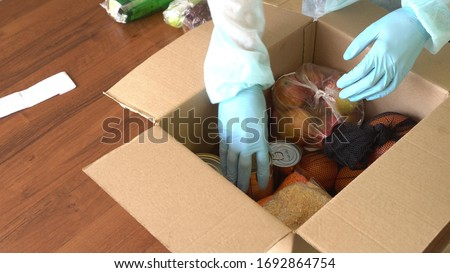 Takeaway and door delivery of goods. Order picker in protective suit, hand gloves and mask. Coronavirus disease (COVID-19) pandemic. Online contactless food shopping