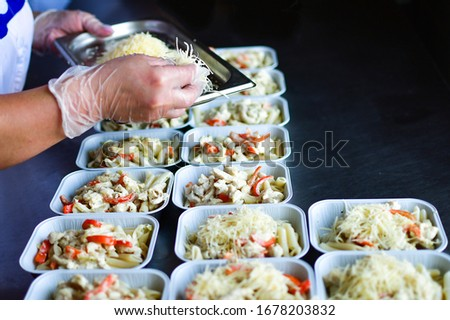takeaway chicken salad with vegetables and cheese food delivery. preparing portions in containers. service food order online delivery in quarantine covid-19. airline food. airline meals and snacks