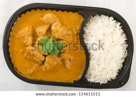 Takeaway Curry - Chicken curry with coconut milk and plain rice in a plastic container on a white background. Shot from above.