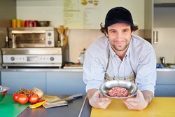 Takeaway food entrepeneur standing proudly next to a bowl of fresh high-quality minced red meat with which he makes his hamburger patties