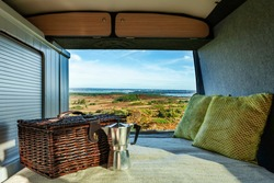 Taken from a camper van with a hamper, stove top coffee maker and cushions, overlooking the view at Poole harbour, on a bright Autumn day