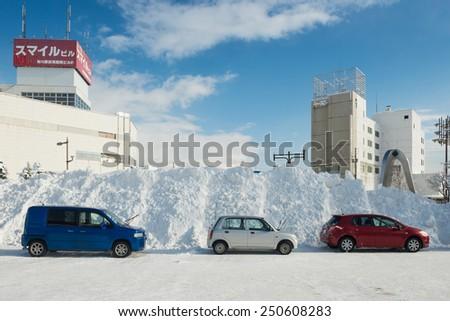 TAKIKAWA, HOKKAIDO, JAPAN - JANUARY 10, 2015: Snow piled higher than cars. Hokkaido is the most snowy area in Japan.
