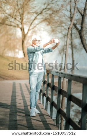 Taking a photo. Joyful stylish elderly woman with short silver haircut and denim outfit taking a photo standing on the park bridge