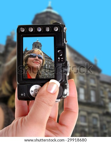 Taking a photograph of a woman in Amsterdam with a point and shoot camera, hand is finely manicured