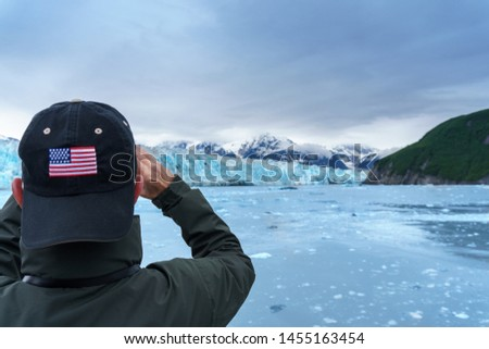 Taking a picture of Hubbard Glacier, Man is wearing a cap with use flag. Expedition to the glaciers of Alaska. Green mountain and snowy glacier looks amazing. It is summer time cruise.