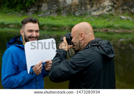 Taking a picture or a photo shoot in the open air. A bald male photographer is photographing a model of a bearded guy holding a mocap sign for text.