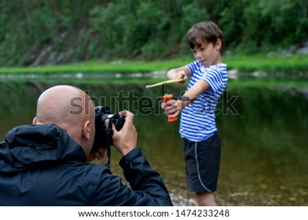 Taking a picture or a photo shoot in the open air. A bald male photographer photographs a 9-year-old boy with a slingshot in his hands on a background of a mountain landscape
